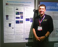 David Eardley standing with his poster case study for 3D printed orthotics in an elite runner